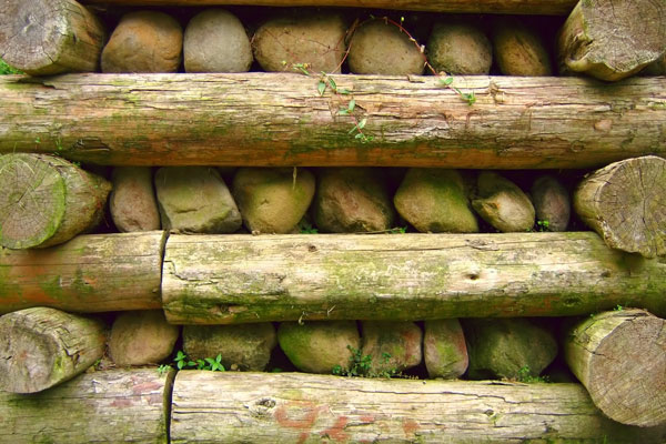 Retaining wall built with wooden posts and stones