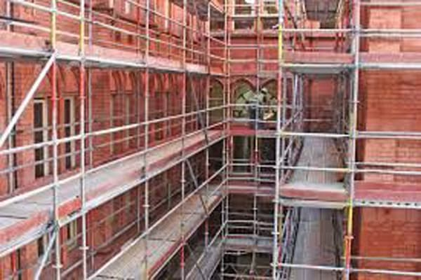 Brick building covered in metal and timber scaffolding